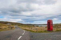 Leere Landschaftsstraße mit britischer roter Telefonzelle Lizenzfreie Stockfotografie