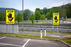 Leere Landstraße in der österreichischen Landschaft mit dem Halt/falschen dem Zeichen des END FALSCH, die Fahrer zu warnen stockbilder