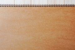 Leere leere braune Titelseiteabdeckung des gewundenen en-gehend Notizblockes auf dem hölzernen Hintergrund lizenzfreie stockbilder