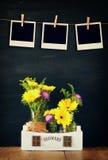 Leere leere sofortige Fotos hängen an einem Seil über Sommerblumenstrauß von Blumen auf dem Holztisch mit schwarzem Hintergrund Lizenzfreies Stockbild