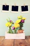 Leere leere sofortige Fotos hängen an einem Seil über Sommerblumenstrauß von Blumen auf dem Holztisch mit tadellosem Hintergrund  Stockfotografie