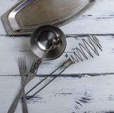 Leere Metallobjekte der Küche auf einem weißen hölzernen Hintergrund stockfoto