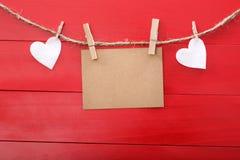 Leere Mitteilungskarten- und -filzherzen mit Wäscheklammern Stockfoto