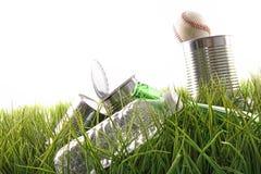 Leere Nahrungsmitteldosen, -flaschen und -baseball im Gras Stockfoto