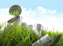 Leere Nahrungsmitteldosen im Gras mit blauem Himmel Stockfotografie
