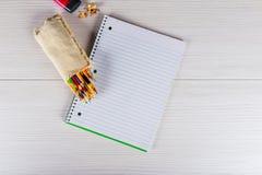 Leere Notizblock- und Bleistiftfarbe auf hölzernem blackground Lizenzfreies Stockbild