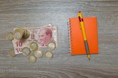 Leere Notizbuchseite und Stift und türkische Lira auf hölzernem Bürotisch Draufsicht mit Kopienraum Stockfoto