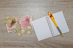 Leere Notizbuchseite und Stift und türkische Lira auf hölzernem Bürotisch Draufsicht mit Kopienraum Stockbilder
