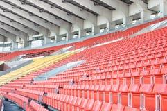 Leere orange und gelbe Sitze am Stadion Stockfotos