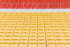 Leere orange und gelbe Sitze am Stadion Stockbilder