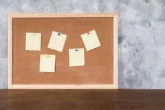 Leere Papiere stecken oben auf Korkenbrett über Holztisch mit Beschaffenheit fest Lizenzfreies Stockfoto