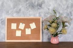 Leere Papiere stecken oben auf Korkenbrett und Blumenvase über hölzernem ta fest Stockfotografie