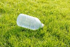 Leere Plastikflasche auf einem gr?nen Rasen Konzept: Umweltverschmutzung lizenzfreies stockbild