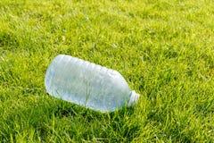 Leere Plastikflasche auf einem gr?nen Rasen Konzept: Umweltverschmutzung lizenzfreie stockfotografie
