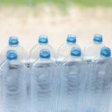 leere Plastikwasserflaschen auf Tabelle - Wiederverwertungs- und Lebensmittelspeicher Stockbilder