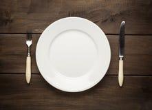 Leere Platte auf einem Holztisch mit Gabel und Messer Lizenzfreie Stockbilder