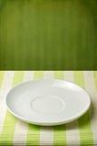 Leere Platte auf gestreifter Tischdecke Lizenzfreies Stockfoto