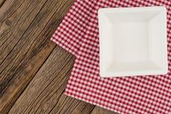 Leere Platte auf hölzerner Tischplatte mit Tischdecke Lizenzfreies Stockfoto