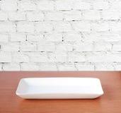 Leere Platte auf hölzerner Tabelle über weißem Backsteinmauerhintergrund, Lebensmittel Stockfotos