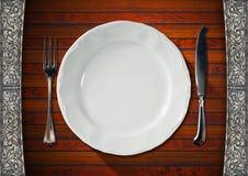 Leere Platte auf Holztisch mit Tischbesteck Stockfoto