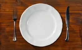 Leere Platte auf Holztisch mit Tischbesteck Lizenzfreies Stockbild