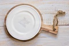 Leere Platte der weißen Weinlese auf rundem Schneidebrett, über weißem hölzernem Hintergrund, Provence-Art, flache Lage Lizenzfreie Stockfotografie