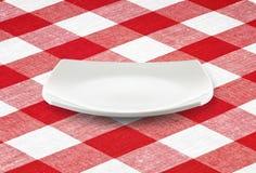 Leere Platte des weißen Quadrats auf roter Ginghamtischdecke Lizenzfreie Stockfotografie