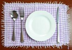 Leere Platte mit Gabel, Messer und Löffel Stockfoto