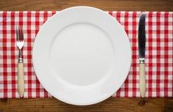 Leere Platte mit Gabel und Messer auf Tischdecke vorbei Stockfoto