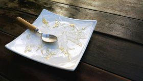 Leere Platte mit Krümeln des gegessenen Kuchens und des benutzten Löffels Lizenzfreie Stockfotos