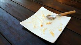 Leere Platte mit Krümeln des gegessenen Kuchens und des benutzten Löffels Stockfotografie