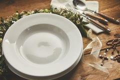 Leere Platte, Teller und Tischbesteck mit christlichen Symbolen für Taufe oder heilige Kommunion Stockbilder