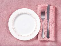 Leere Platte, Tischbesteck und Serviette auf rosa konkretem Hintergrund lizenzfreie stockfotografie