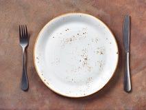 Leere Platte und Tischbesteck auf konkretem Hintergrund des braunen Schmutzes lizenzfreie stockfotografie