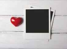 Leere polaroidfotos mit rotem Herzen Stockfoto