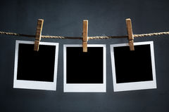Leere polaroidphotographien, die an einer Wäscheleine hängen Stockbilder