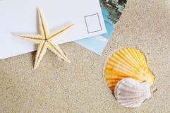 Leere Postkarte auf Sand Stockfotos