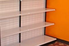 Leere Regale im Supermarkt mit orange Wänden stockbilder