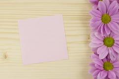 Leere rosa Karte und rosa Blumen auf hölzernem Hintergrund Stockfotos