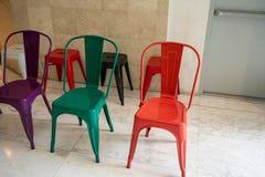 Leere rote, grüne, schwarze, weiße und purpurrote Metallstühle lizenzfreie stockfotos
