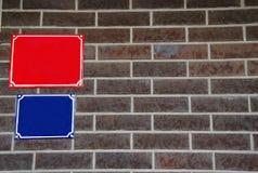 Leere rote und blaue Hausnummer unterzeichnet auf einer Ziegelsteindunkelheitswand lizenzfreies stockbild