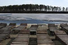 Leere Ruhesessel auf dem Strand während Eis auf dem See stockfotos