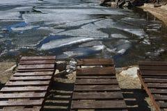 Leere Ruhesessel auf dem Strand während Eis auf dem See stockbilder
