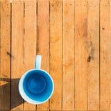 Leere Schale auf altem hölzernem Brett Blauer Becher auf hölzernem Lizenzfreie Stockfotografie