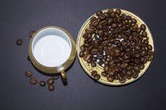 Leere Schale, Untertasse, Kaffeebohnen auf einem schwarzen Hintergrund Lizenzfreie Stockfotografie