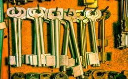 Leere Schlüssel der langen Weinlese, die an einer Schraube an einem hölzernen braunen Brett in der Werkstatt hängen Stockfoto
