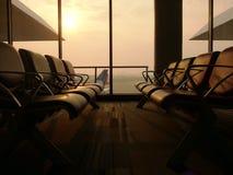 Leere Sitze in Flughafenwarteaufenthaltsraum mit Flughafen und Flugzeugen im Hintergrund unter weicher Sonne beleuchten Stockfotos