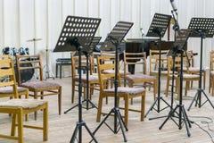 Leere Sitze und einige Instrumente im Auditorium, das Orchester erwartet, um auf das Stadium zu kommen schwarzes Notenpult auf St stockfotos