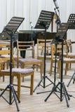 Leere Sitze und einige Instrumente im Auditorium, das Orchester erwartet, um auf das Stadium zu kommen schwarzes Notenpult auf St lizenzfreie stockfotos