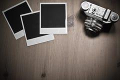 Leere sofortige Fotorahmen des Stilllebens drei auf altem hölzernem Hintergrund mit alter Retro- Weinlesekamera mit Kopienraum Lizenzfreies Stockfoto